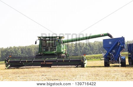 Harvester machine to harvest wheat field working. Combine harvester agriculture machine harvesting golden ripe wheat field. Agriculture