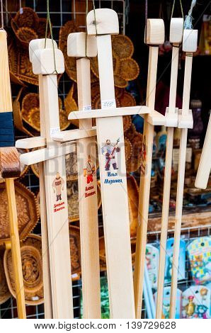 VELIKY NOVGOROD RUSSIA-JULY 22 2016. Souvenir trade - wooden souvenir swords with images of the heroes of Russian fairy tales