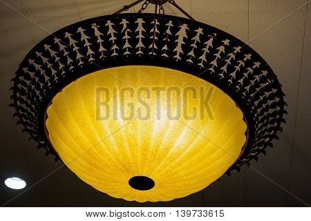 Ornate yellow ceiling dome light shade, with a white down-light nearby.
