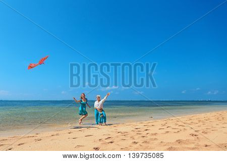Happy family on beach - grandmother mother and baby girl have fun woman run along sea surf with water splashes launching bird kite. Active parent and people activity on summer holiday with children