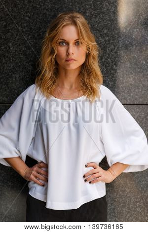 Outdoors portrait of elegant blonde woman in half growth with hands akimbo