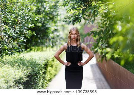 Outdoors portrait of young girl with blond hair in half growth with hands akimbo. Shoot on fast aperture