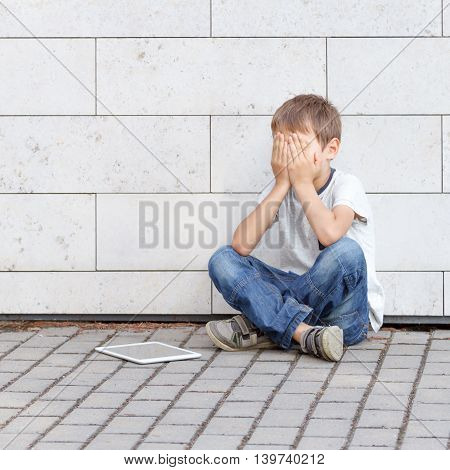 Little boy sad, tired and stressed with tablet computer PC. Kid sitting on the ground, holding his head, close eyes. Casual wear. Outdoor. Education, learning, technology, addiction concept
