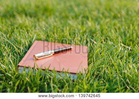 Pen and Notebook on Fresh Green Grass. Education Concept