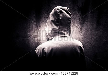 Back side of mysterious woman wearing hoodie hiding in the dark,Scary background for book cover