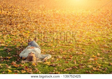 Woman listening music on grass at autumn time