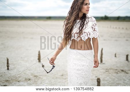 Portrait of a beautiful brunette in a white lace dress. Girl walking on sandy estuary looked like a desert. In the hands of sunglasses.