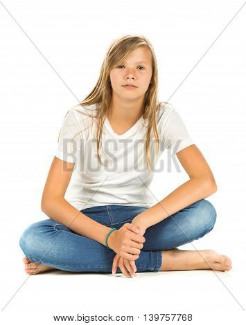 Young girl sitting barefoot with white t-shirt and blue jeans over white background