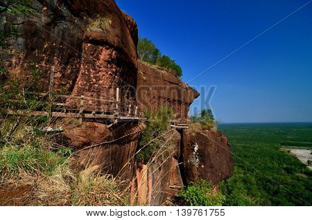 The high rock moutain with hanging wooden bridge attached on the cliff under clear blue sky shot in Thailand tourist destination