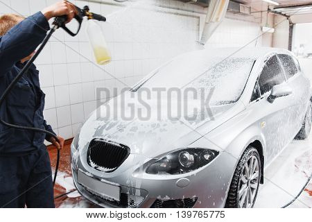 Serviceman in carwash washing car with hose. Handle automobile cleaning at special store, complex service