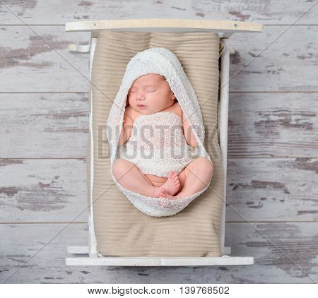 infant girl in white asleep on a small crib