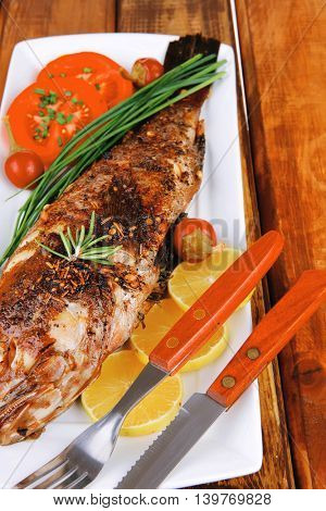 served main course on wood: whole fried seabass on plate with lemons,tomatoes and peppers