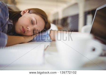 Close-up of tired businesswoman taking nap on desk in creative office