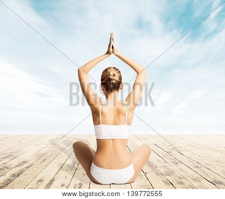 Beautiful woman with a perfect body meditating on a pier. Yoga, sport and summer concept.