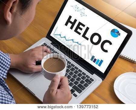 HELOC (Home Equity Line of Credit) Businessman at work. Close-up top view of man working on laptop while sitting at the wooden desk coffee poster