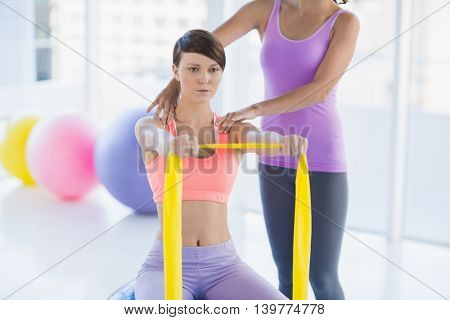 Woman with trainer holding resistance band at fitness studio