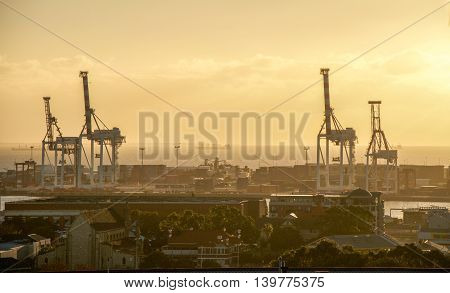 FREMANTLE,WA,AUSTRALIA-JUNE 25,2016: Fremantle port with large gantry cranes, sea containers and the Indian Ocean at sunset in Fremantle, Western Australia.