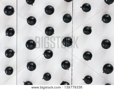 Fresh black currants on white wooden background. blackcurrants pattern for wallpaper. Flay lay or top view