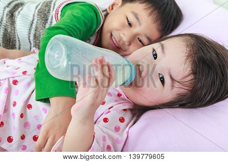 Closeup asian sibling having happy in bed before sleeping. Sister suck up milk. Brother hug his sister. Conceptual image about loving and bonding of sibling. Happy family spending time together.