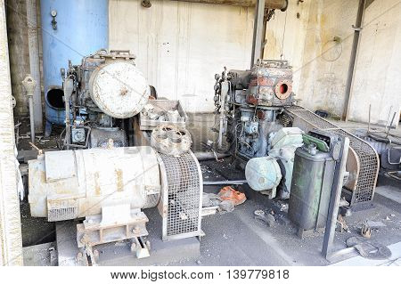 Old abandoned air compressor station with two electric motor compressors.