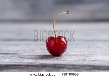 Wet cherry on gray surface. Clean red fruit. High amount of melatonin. Small drops of water.