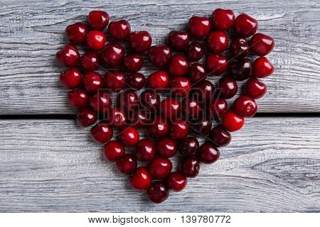 Heart made of cherry. Dark fruit on wooden surface. Summer fills heart with joy. Make life brighter.