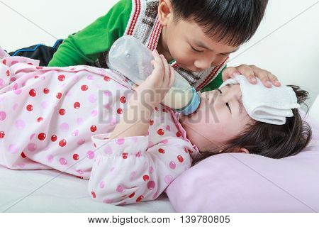 Sick sister lying and suck up milk on the bed kindly brother keep vigil over a sick of closely. Conceptual image about loving and bonding of sibling.
