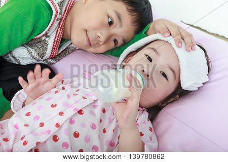 Sick Sister Lying And Suck Up Milk On The Bed, Kindly Brother Keep Vigil Over A Sick Of Closely.