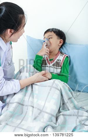 Asian Boy Having Respiratory Illness Helped By Health Professional With Inhaler.