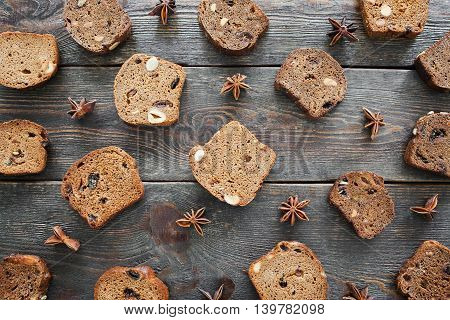Sweet rye bread slices on wooden background, flat lay. Top view on dark soft tack loaves with hazelnut and raisins and anise stars on old rustic table. Nice bakery backdrop