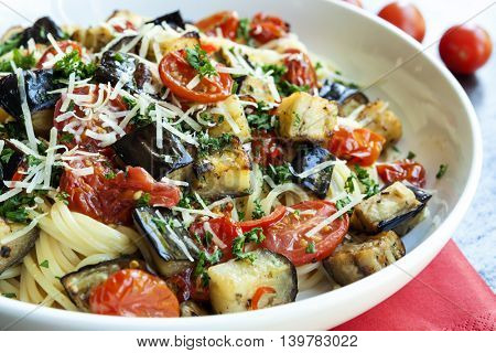 Spaghetti with roasted eggplant or aubergine and cherry tomatoes.  Topped with shaved parmesan.  Side view.