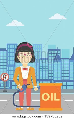 An asian woman standing near oil barrel. Woman holding gas pump nozzle on a city background. Woman with gas pump and oil barrel. Vector flat design illustration. Vertical layout.