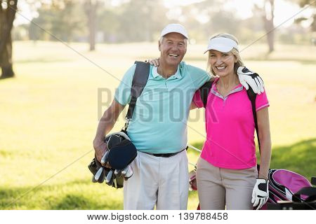 Happy mature golfer couple with arm around while standing on field