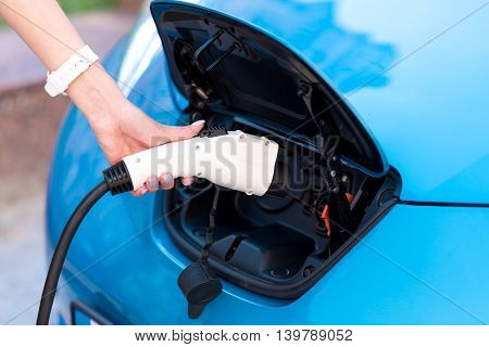 Lets charge it. Close up of a hand of a woman holding a charging cable and thrusting it in her electric car