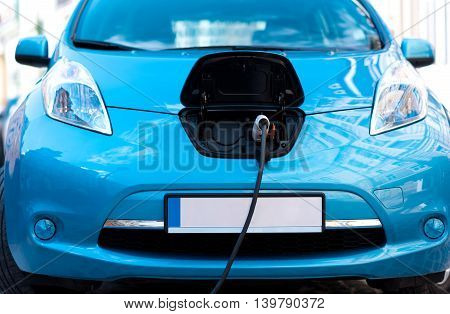 Keep up with the times. Close up of a electric car plugged to power connector for charging the battery on the street