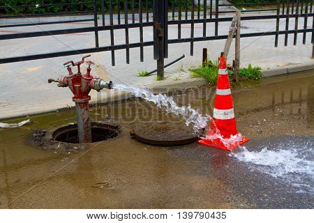 Traffic cone and old red fire hydrant in manhole cover.