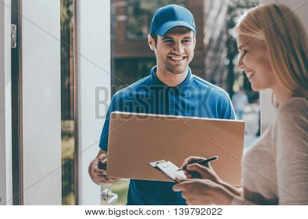Signing to get her package. Smiling young delivery man holding a cardboard box while beautiful young woman putting signature in clipboard