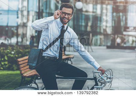 Businessman on bicycle. Side view of smiling young businessman looking at camera and adjusting eyewear while riding on his bicycle