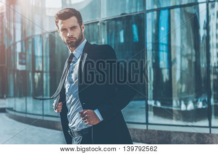 Confident business leader. Confident young businessman adjusting his jacket and looking at camera while standing outdoors with office building in the background