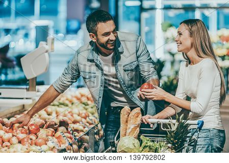 Enjoying time in supermarket. Beautiful young smiling couple choosing apples in supermarket together