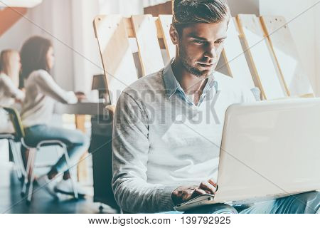 Full concentration at work. Concentrated young man working on laptop while his colleagues working in the background