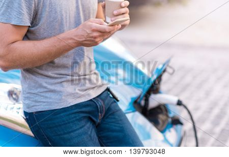 Lets charge it. Close up of hands of a man holding a smartphone and a cup of coffee while charging his electric car