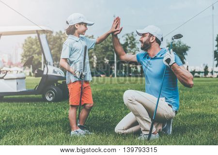 High five! Cheerful young man and his son giving high-five to each other while standing on the golf course