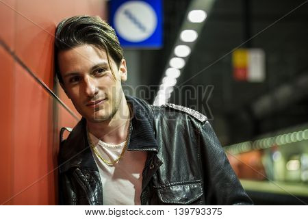 Handsome young male traveler in train station, looking at camera