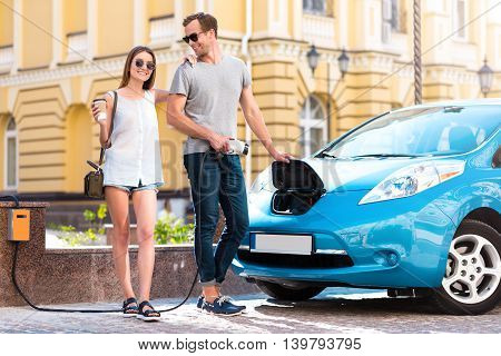 Our new purchase. Pretty charming young woman with coffee looking at the camera while delighted man holding a power cable to the electric car poster