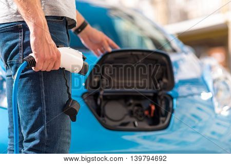 Easy mechanism. Close up of a man who closing a fuel tank with one hand and holding a power connector of an eco car with other