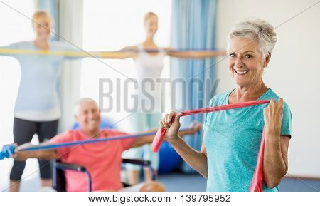 Seniors exercising with stretching bands during sports class
