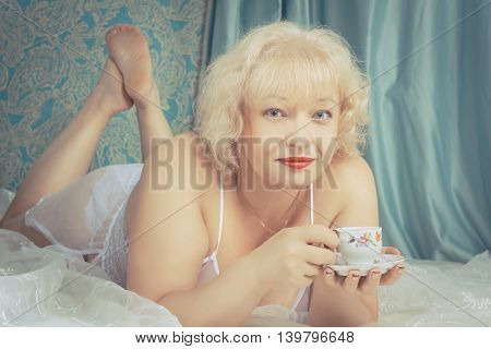 Seductive mature lady laying in her bed with cup of tea