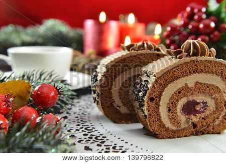 Chocolate roll cakes on Christmas table with candles