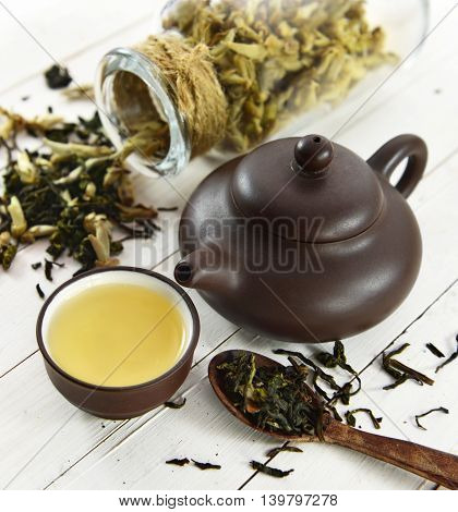 Still life with small cup of green tea, brown tea pot and spoon full of raw tea leaves, chinese tea concept